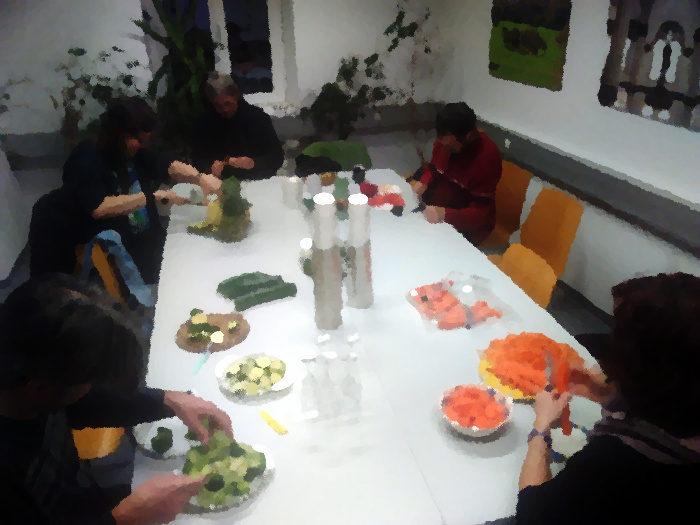 Leute um Tisch, die Gemüse schneiden