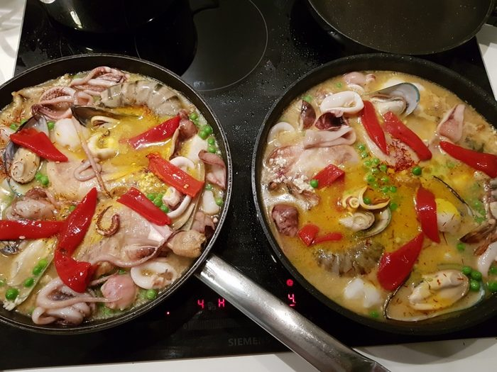 Zwei Pfannen Paella auf dem Herd