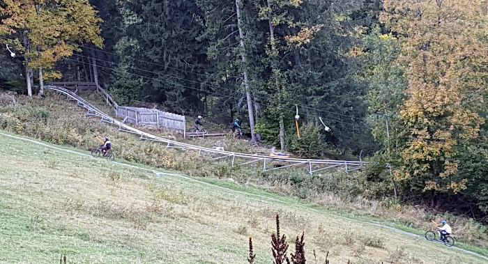 Blick auf Sommerrodelbahn, mit Mountainbikern an Schlepplift